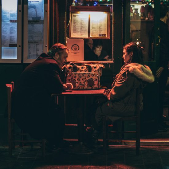 A white man and asian woman discussing the end of their relationship at a dive bar