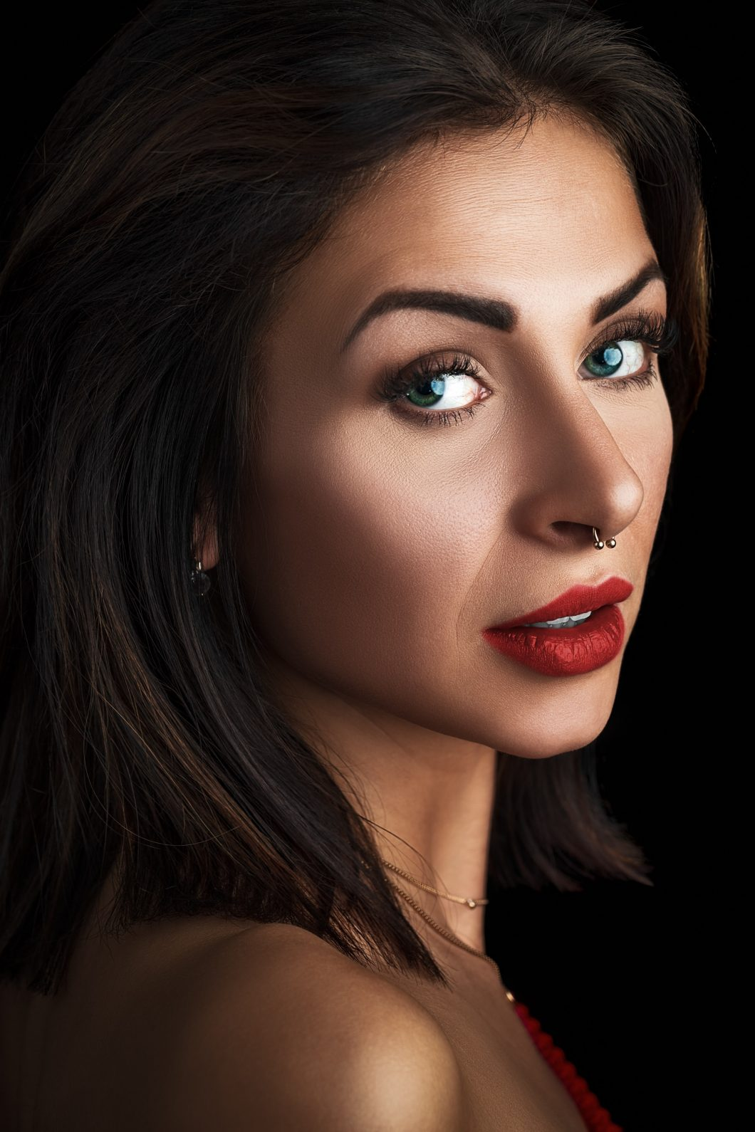 A pretty lady with red lip stick, a nose ring and piercing blue eyes