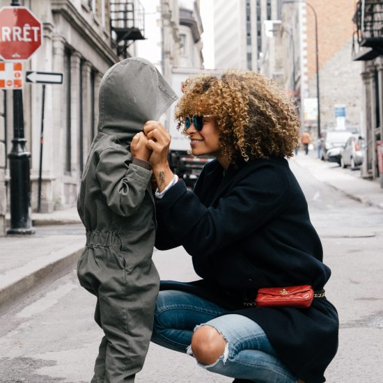 Multi-racial single mom kneeling eye-level to look at her daughter