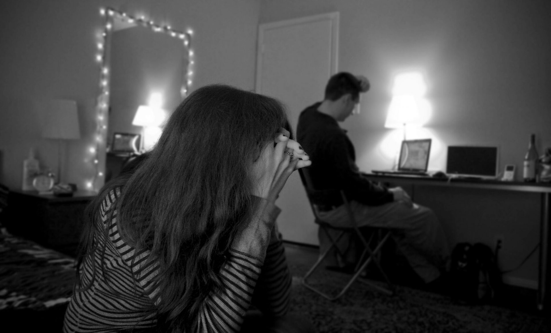 A couple trying to resolve a conflict as a woman holds her her head down in frustration as her husband sits in front of his laptop in the background.