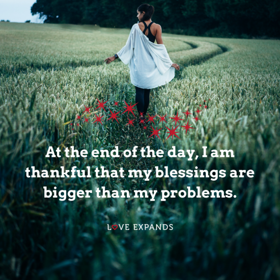 Picture quote of a young lady walking through a green field. The quote is: At the end of the day, I am thankful that my blessings are bigger than my problems.