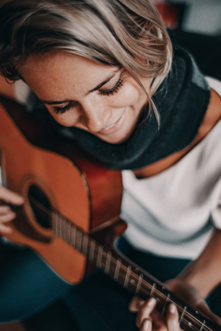 A pretty woman playing her guitar with intention and a smile